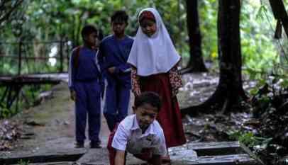 طفل إندونيسي يتحدى الاعاقة ليذهب لمدرسته بزحف 8 كيلومترات يومياً 7